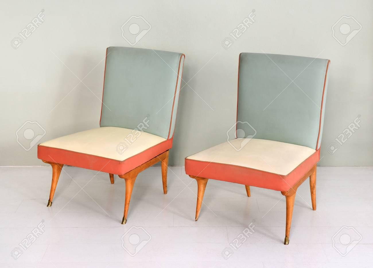 Natura morta di coppia di sedie antiche imbottite retrò con rivestimenti in  vinile in pelle colorata - rosa, blu e bianco - e gambe in legno