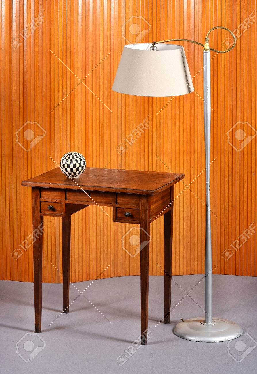 Furniture Still Life Of Metal Floor Lamp With Hanging Shade Beside Small  Wooden Desk With Black