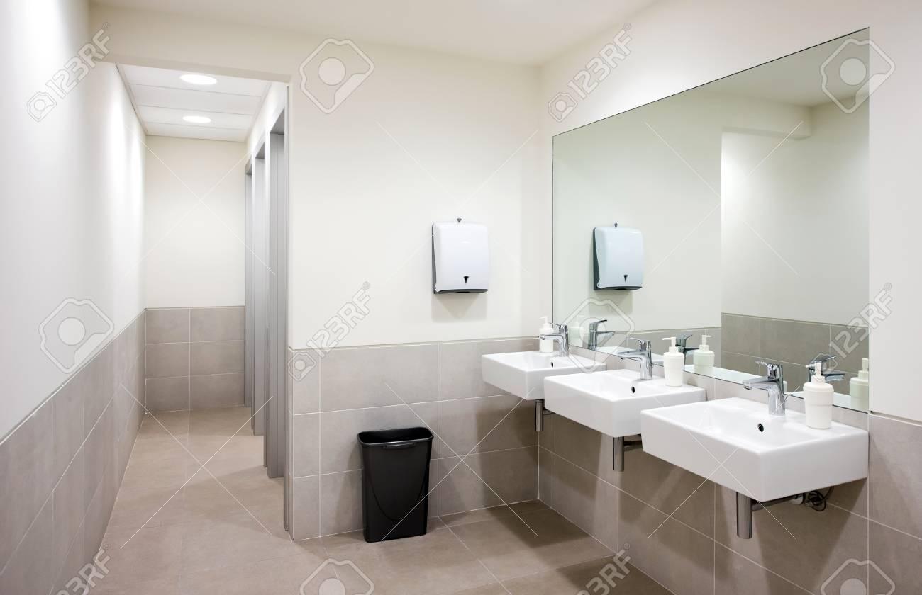 public bathroom mirror. Empty Public Bathroom With White Sinks And Wide Wall Mirror, Air Hand Drier Black Mirror