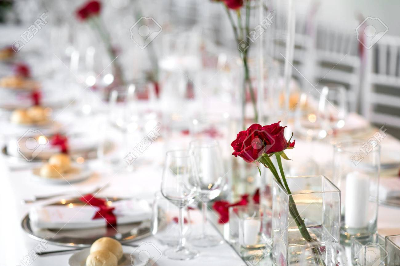 Stock Photo - Stylish formal dinner table setting with red roses serviettes tied with red ribbon and bread rolls set out on side plates amidst assorted ... & Stylish Formal Dinner Table Setting With Red Roses Serviettes ...
