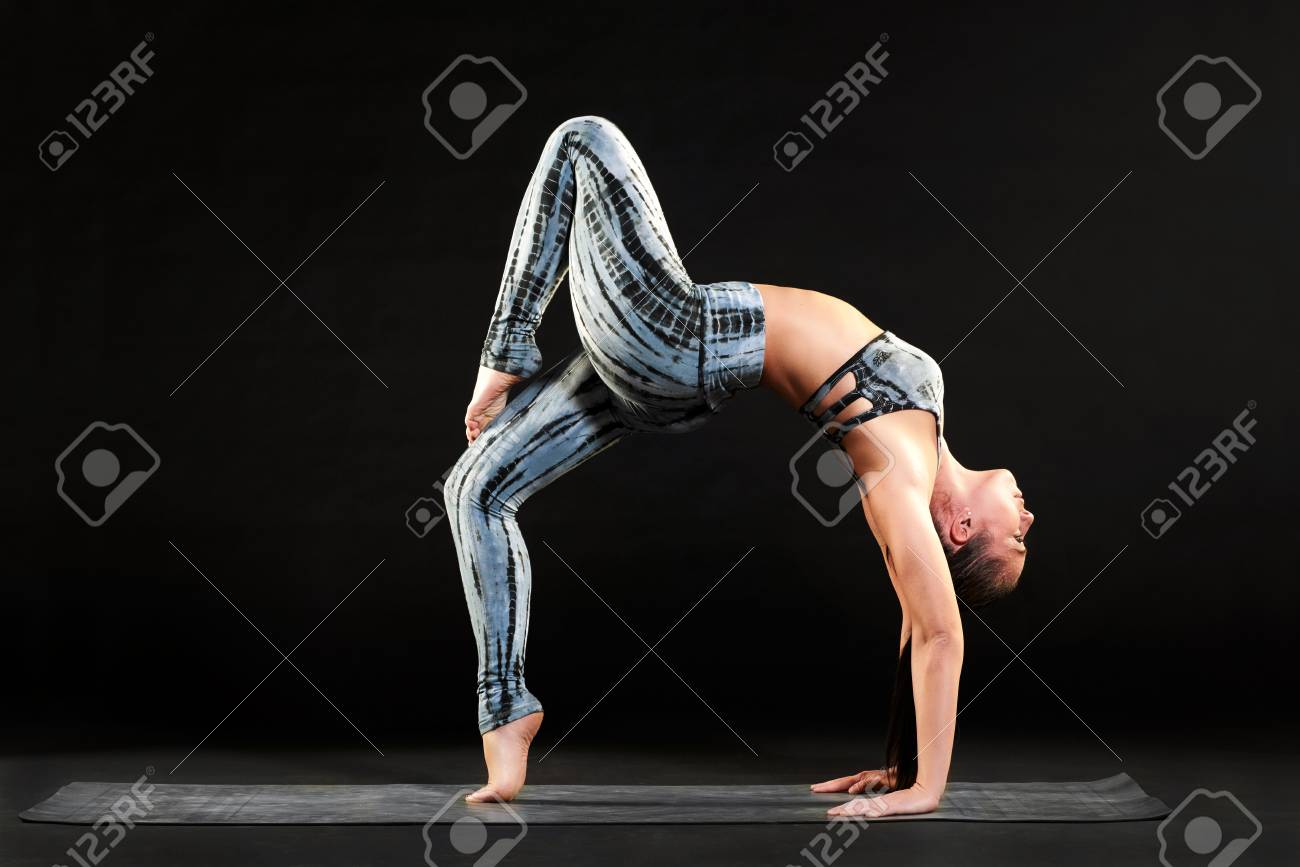 4a3768936ef9b Fit healthy woman doing a one legged wheel pose while working out on a yoga  mat