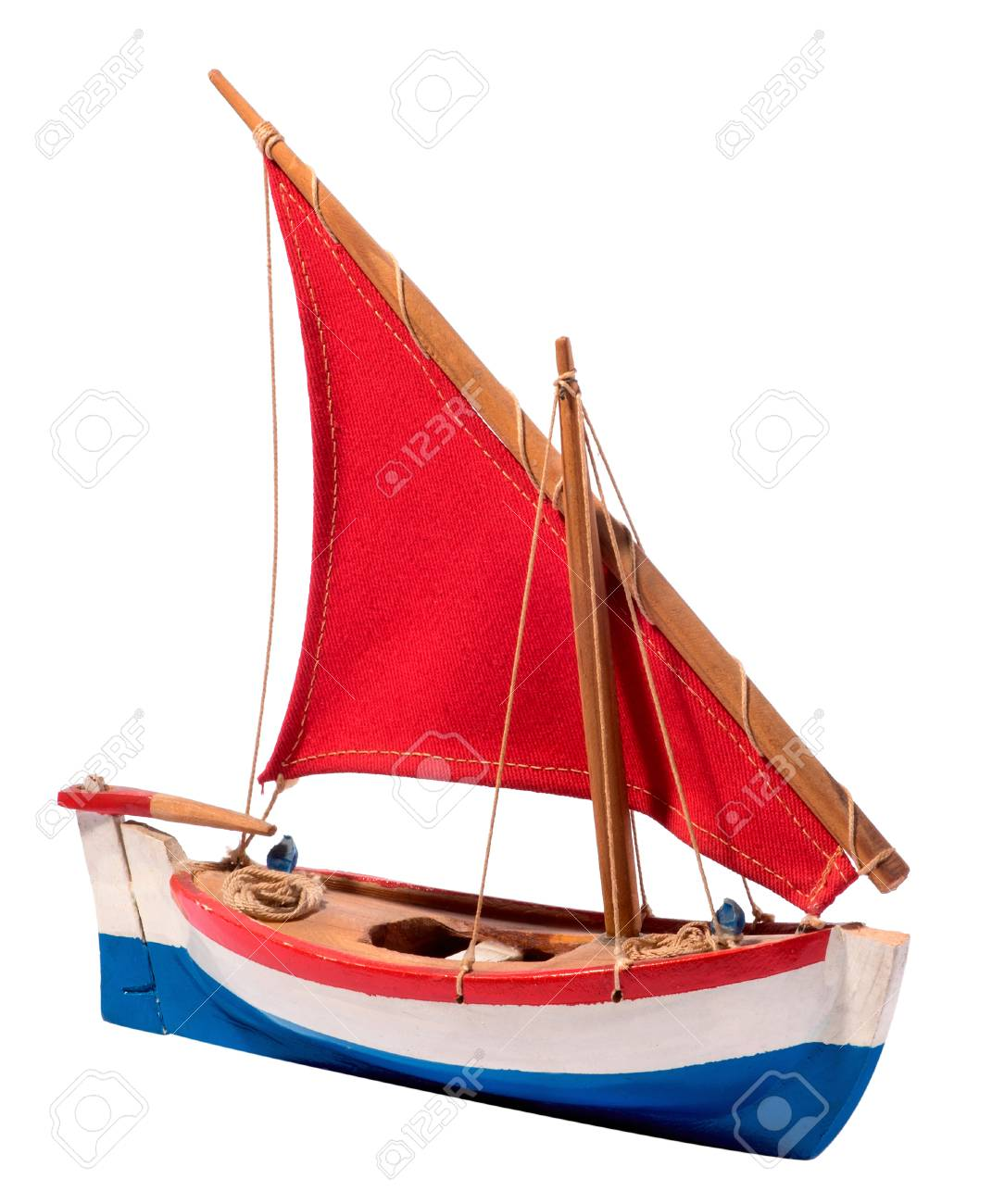 Colorful simple wooden handcrafted sailing boat with red sail