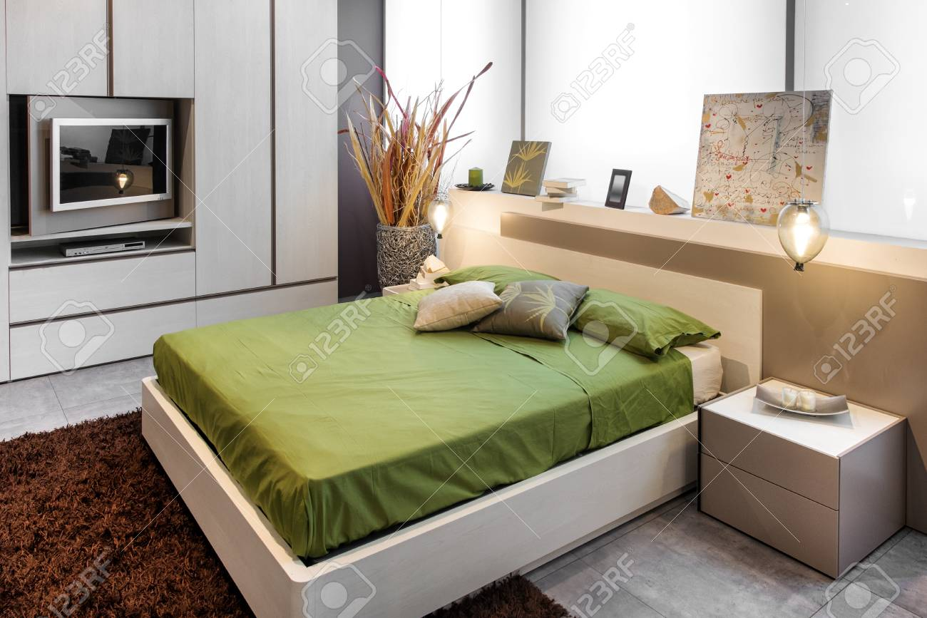 Modern bedroom design with high double bed with green linens..