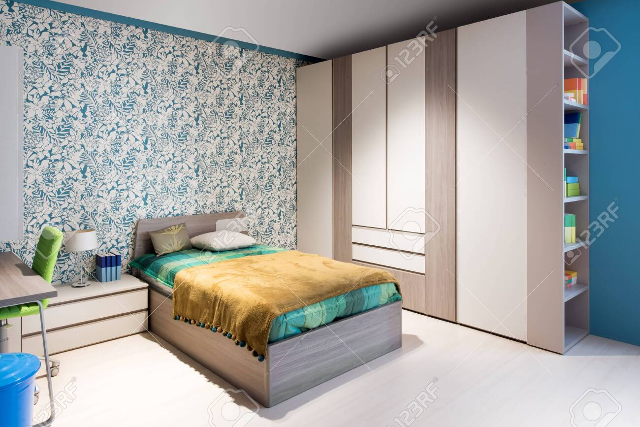 Blue and green themed bedroom interior with feature wall paper,..