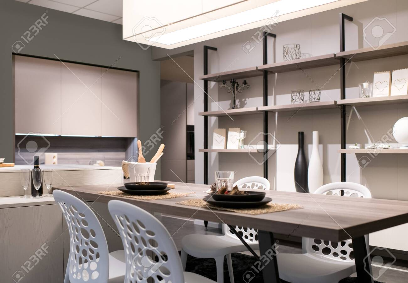 Open plan kitchen and dining room with neutral beige decor, shelving wall unit and a modern table and chairs lit by a large overhead ceiling light - 129305132