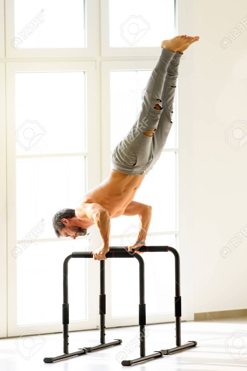 Shirtless Muscular Sportive Man Doing Handstand Push Ups On Bars.. Stock Photo, Picture And Royalty Free Image. Image 140908060.