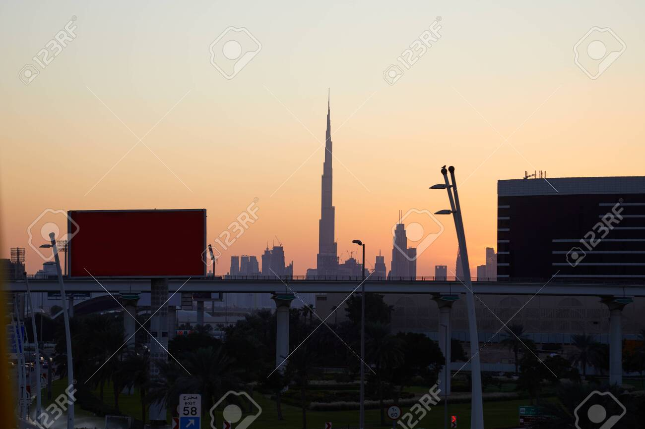 Dubai skyline with Burj Khalifa skyscraper at sunset, clear sky with flyover, billboards and street in United Arab Emirates - 139009430
