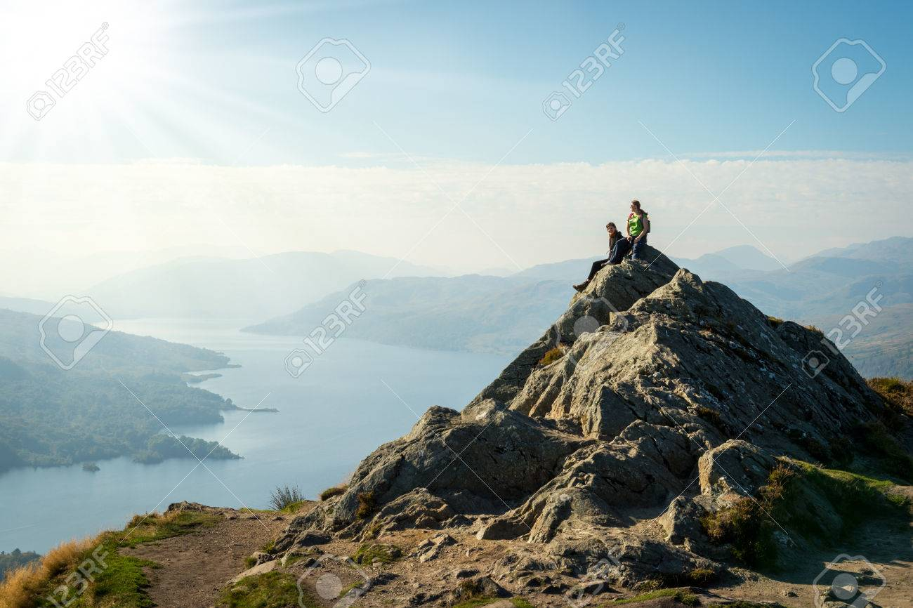 Two female hikers on top of the mountain enjoying valley view, Ben A - 32569501