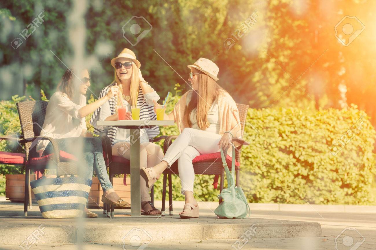Three attractive girlfriends enjoying cocktails in an outdoor cafe, friendship concept - 45233003