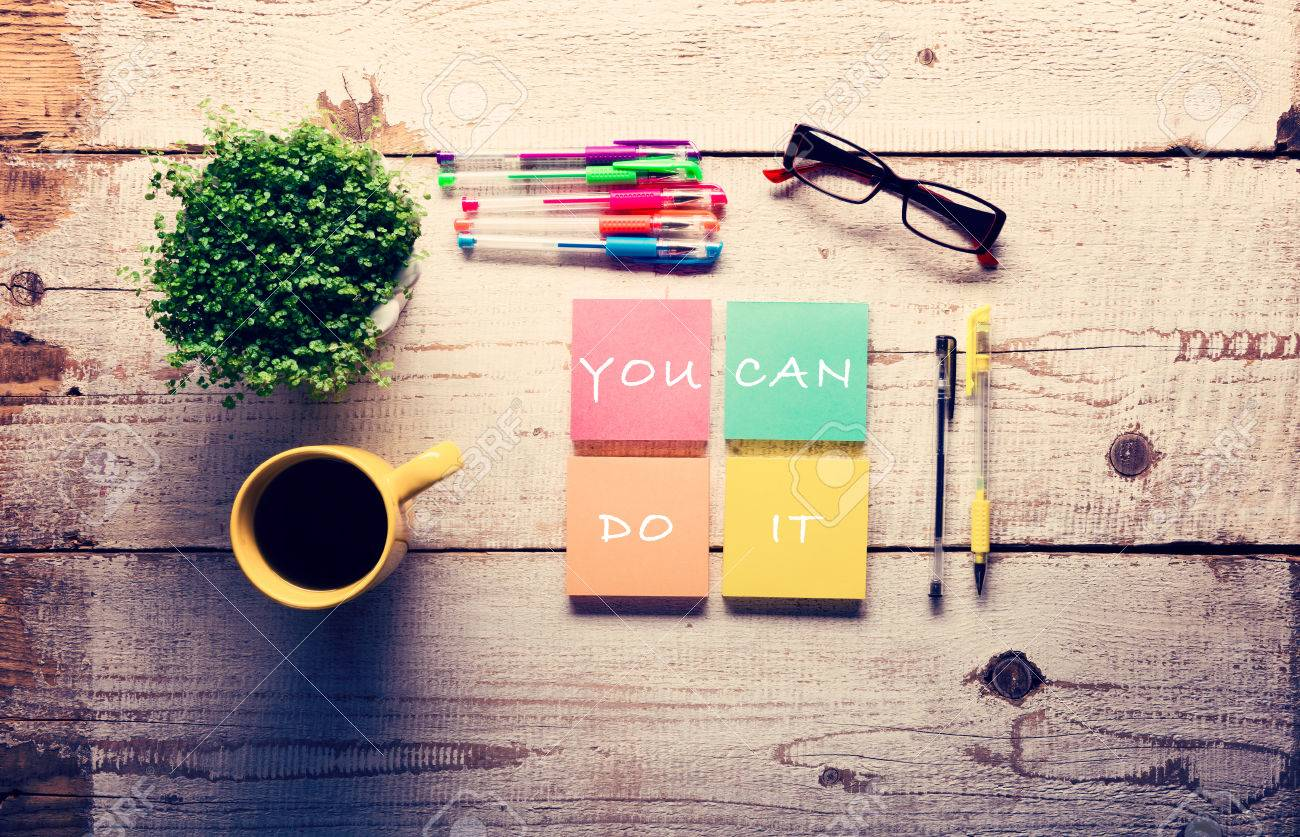 Retro white wooden table with motivational quote on colorful sticky notes, different gel pens and cup of coffee - 56351276