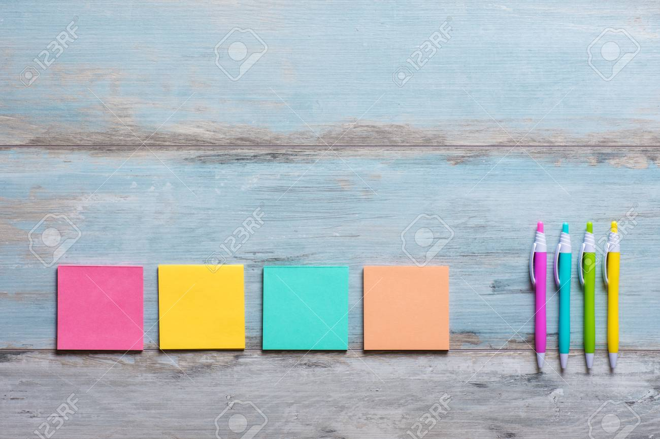 retro blue wooden table with empty colorful sticky notes and stock
