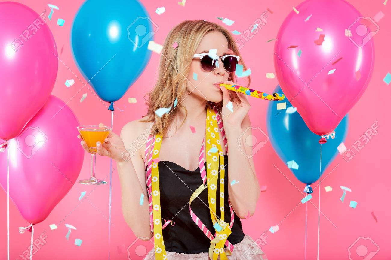 Gorgeous trendy young woman in party outfit celebrating birthday. Party mood, balloons, flying confetti, cocktail and dancing concept on pastel pink background. - 98296732