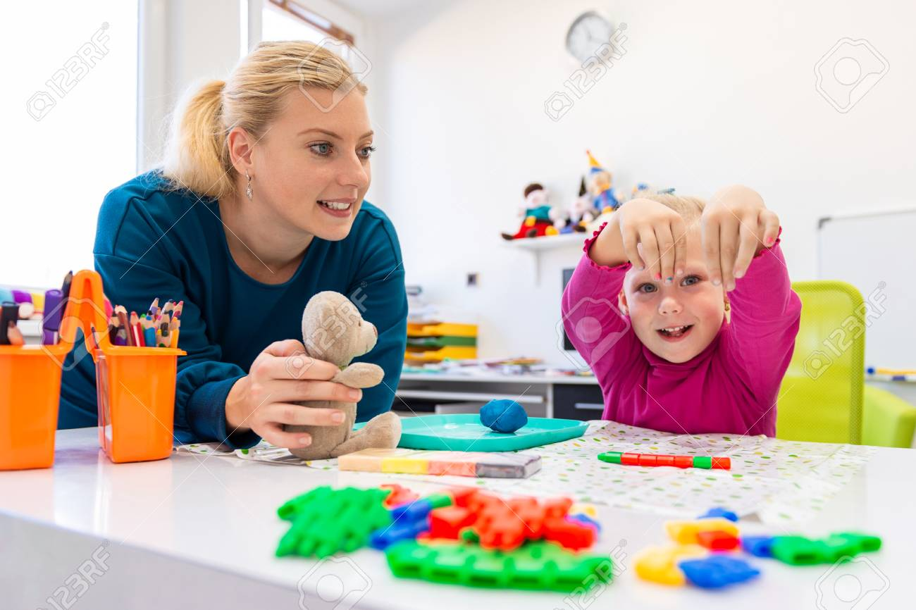 Toddler girl in child occupational therapy session doing sensory playful exercises with her therapist. - 117932507