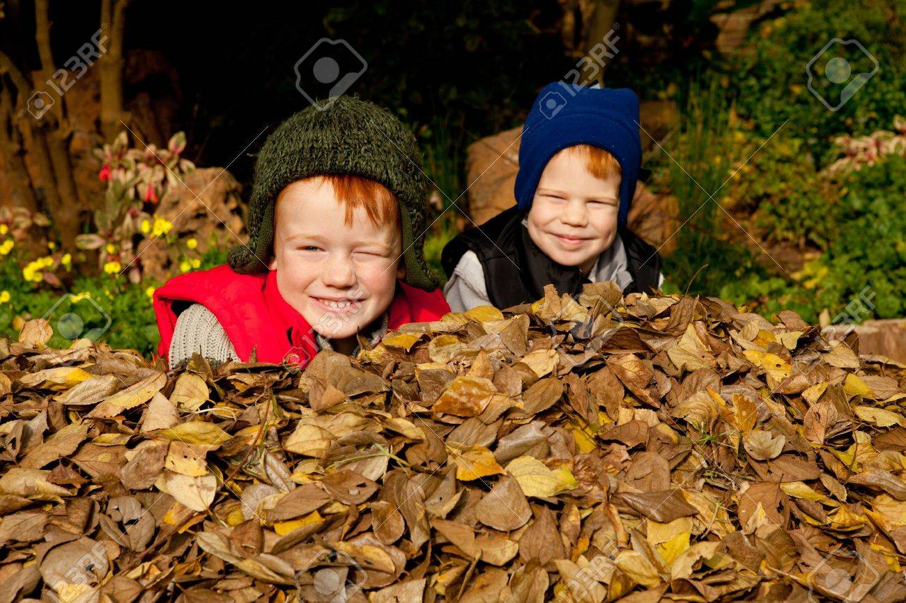 Two happy smiling brothers sit in a heap of colorful autum leaves wearing warm clothes and hats in a park or garden setting Stock Photo - 9516483