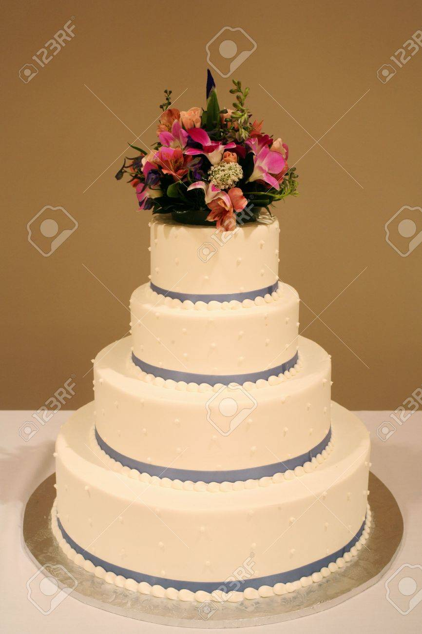 White Wedding Cake With Flowers On Reception Table Stock Photo ...