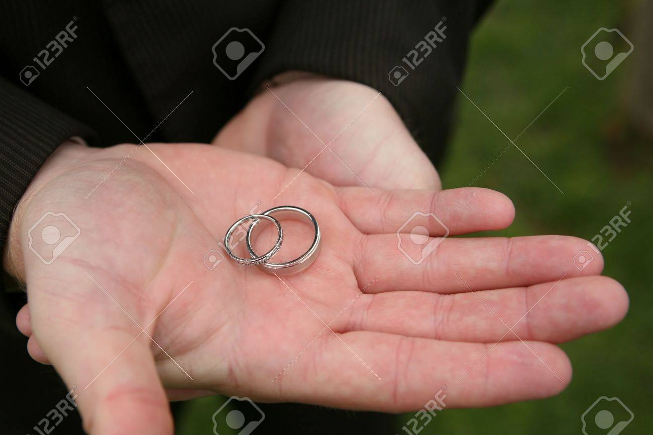 Man\'s Hands Holding Two Silver Wedding Rings Stock Photo, Picture ...