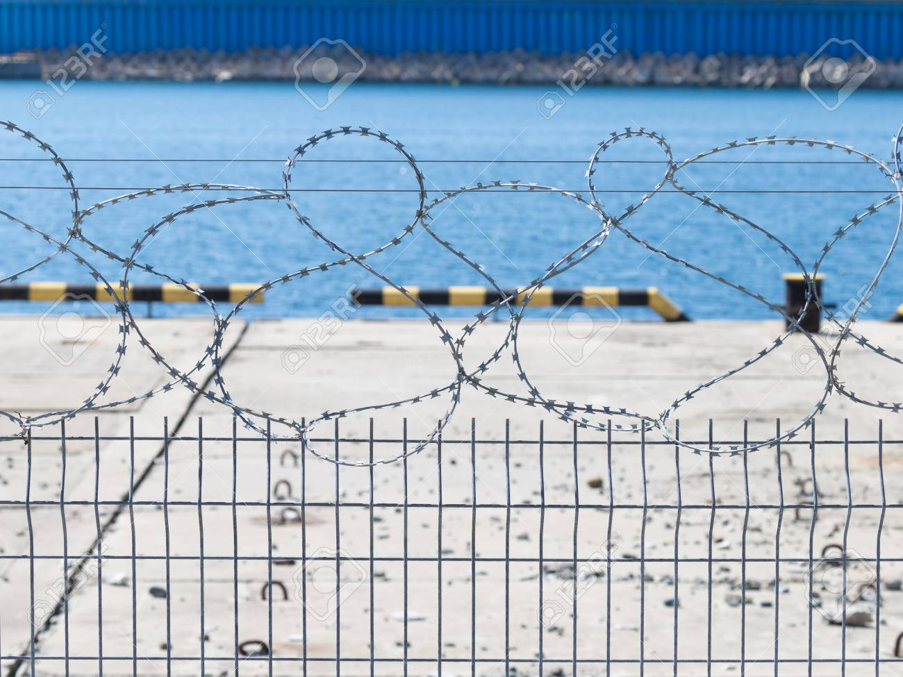 Metal Fence From The Mesh-rabittsi And Barbed Wire On The Background ...