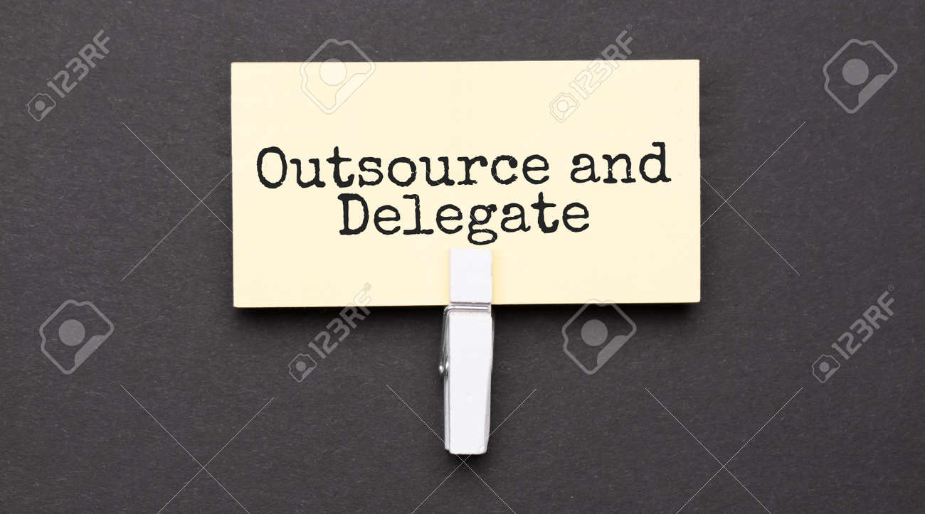 outsource and delegate text on paper with wihte clip. On black background - 173913563