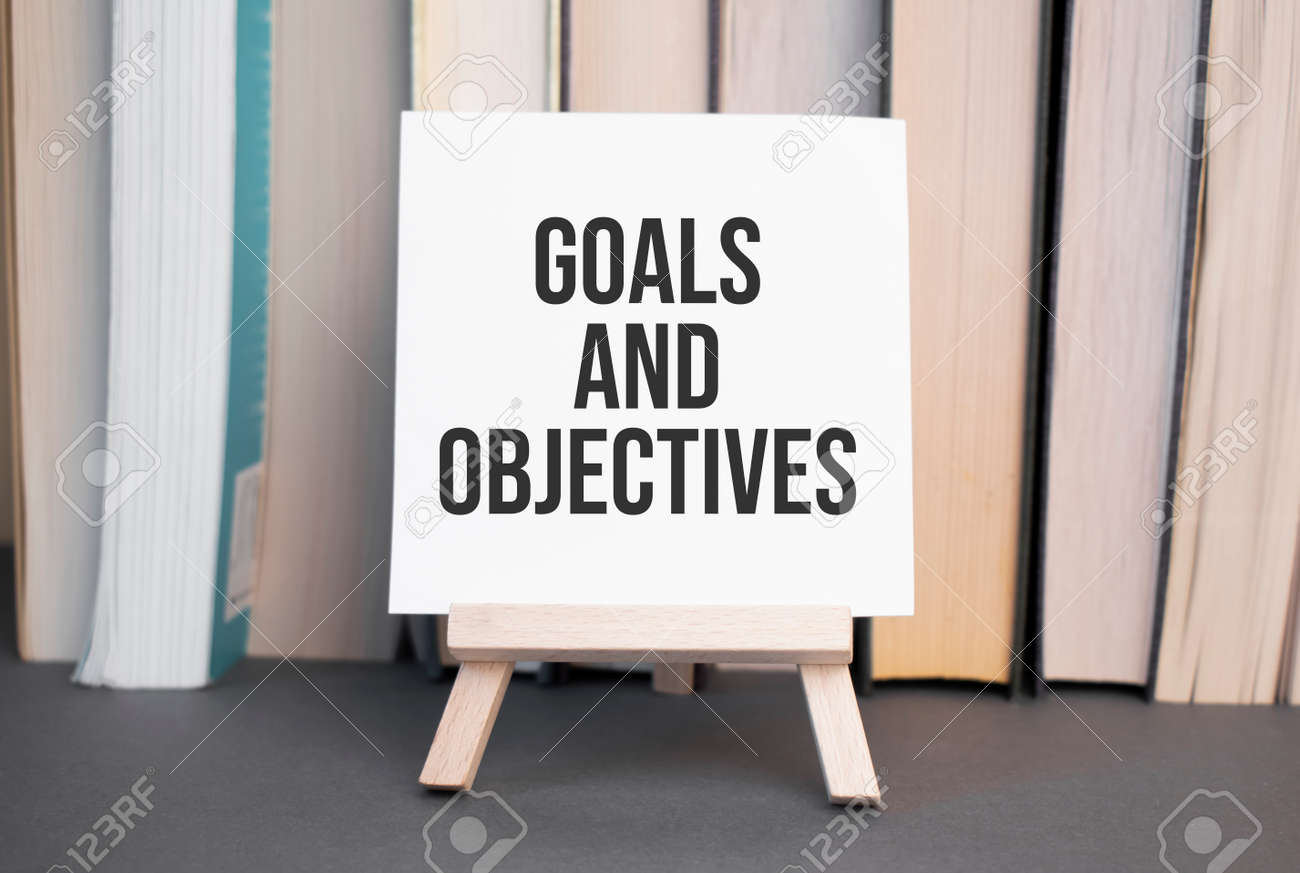 White card with text Goals and Objectives stands on the desk against the background of books stacked - 173913556
