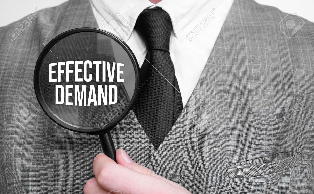 effective demand concept. Businessman hands with magnifier. - 174275249