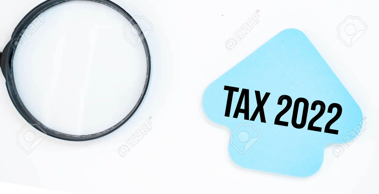 magnifying glass with blue arrow paper sheet with text tax 2022 - 174275258