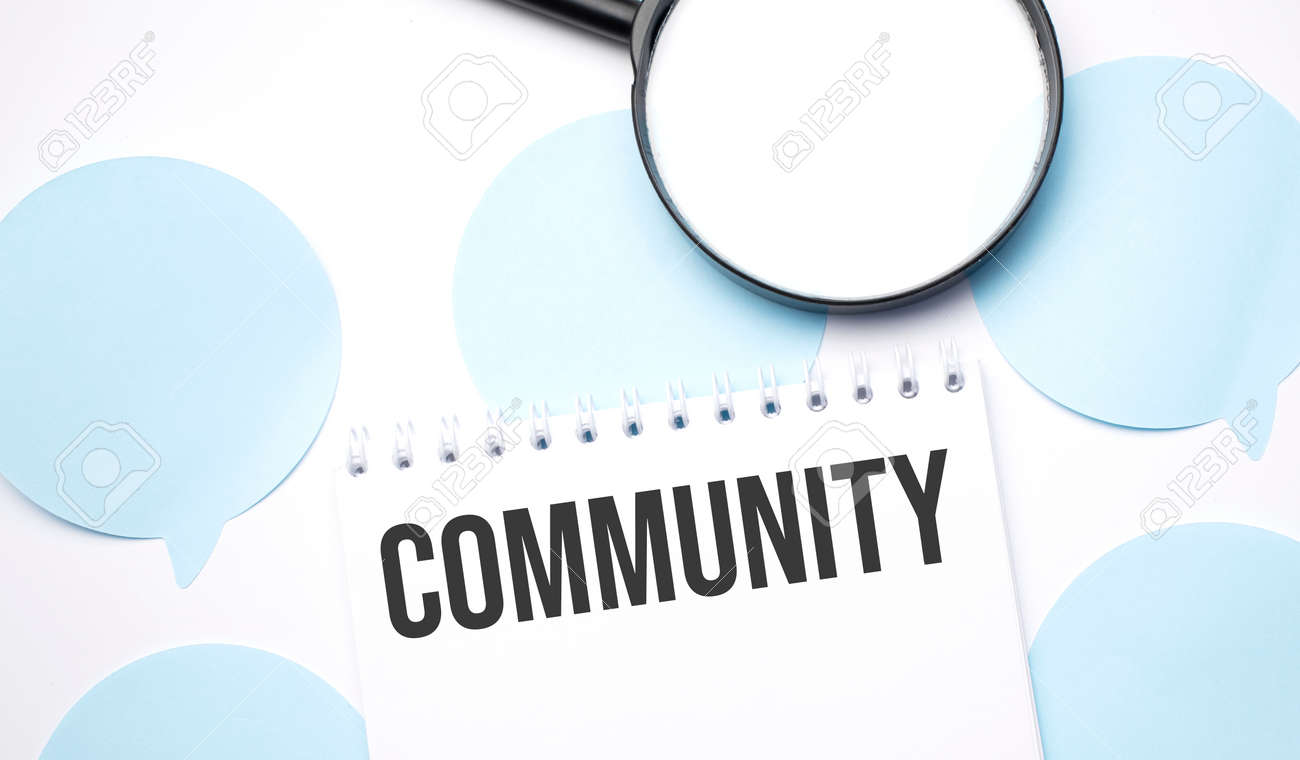 White noteapad and magnifier on blue speech bubles. Text community. Business concept - 174275263