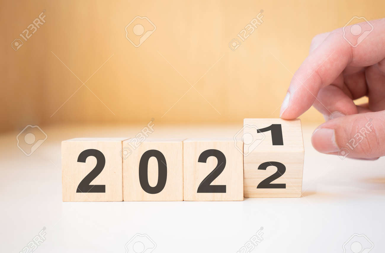 Businessman hand holding wooden cube with flip over block 2021 to 2022 Plans word on table background. - 174275270