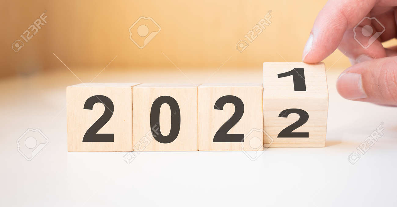 Businessman hand holding wooden cube with flip over block 2021 to 2022 Plans word on table background. - 174274780