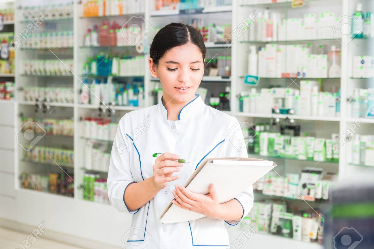 smart and confident woman pharmacist holding a folder and making notes - 141359477
