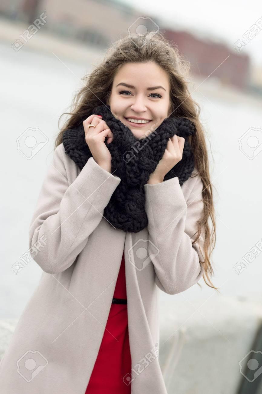 wholesale outlet boutique exquisite design Jeune femme dans un manteau sur la rue souriant à la caméra. Fille dans un  manteau noir, un foulard et une robe rouge contre un ciel gris. Non isolé.  ...