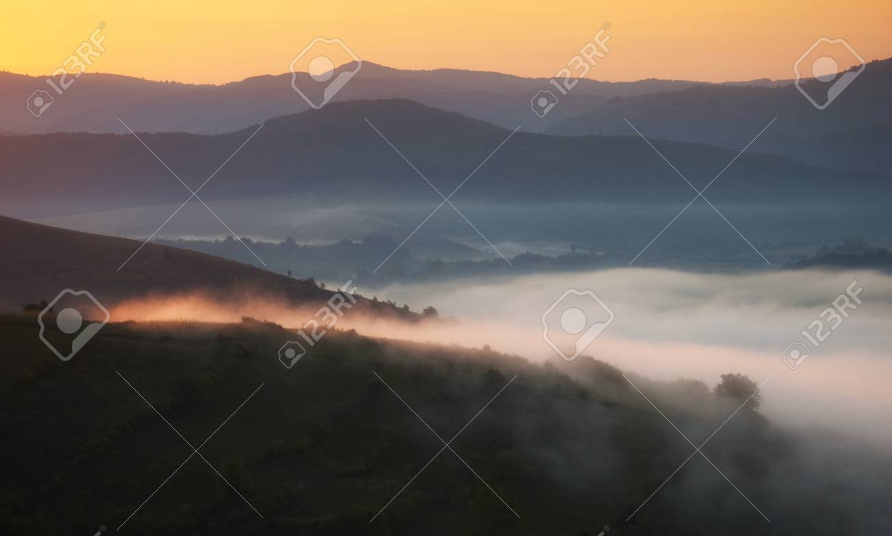 Autumn morning landscape with fog trough hills and first rays of sunlight Stock Photo - 16400280