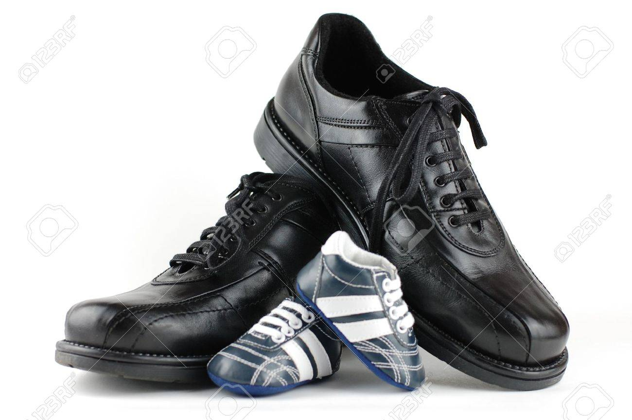 A pair of black man's shoes and a pair of blue baby shoes for the newborn. Father and son concept. Stock Photo - 3818954