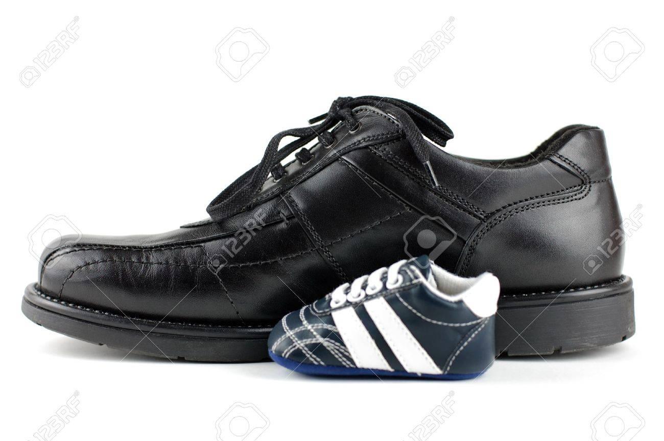 Un homme noir et une chaussure du bébé bleu de chaussures pour le nouveau né. Père et fils conception