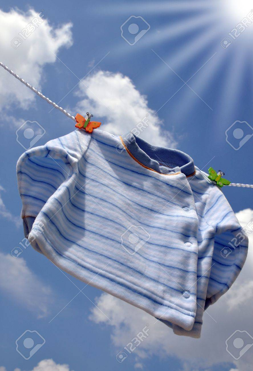 Sun shining on a small blue baby sweater hanging outside Stock Photo - 4739994