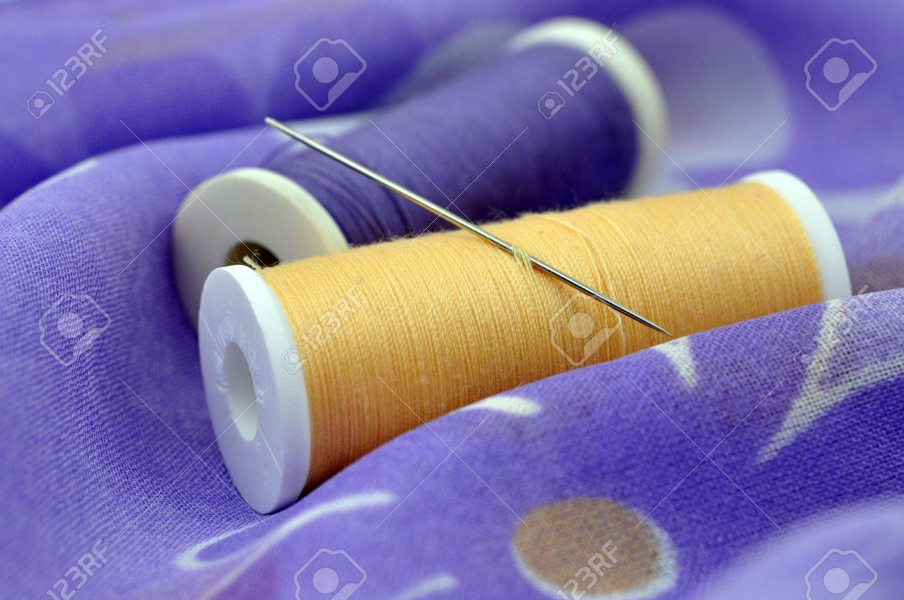 Needle and spools on floral cloth Stock Photo - 6564640