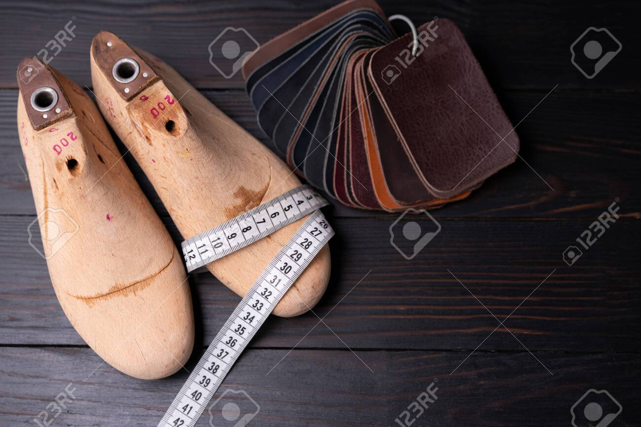 Leather samples for shoes and wooden shoe last on dark wooden table. Designer furniture clothes. Shoe maker workspace. - 148590705