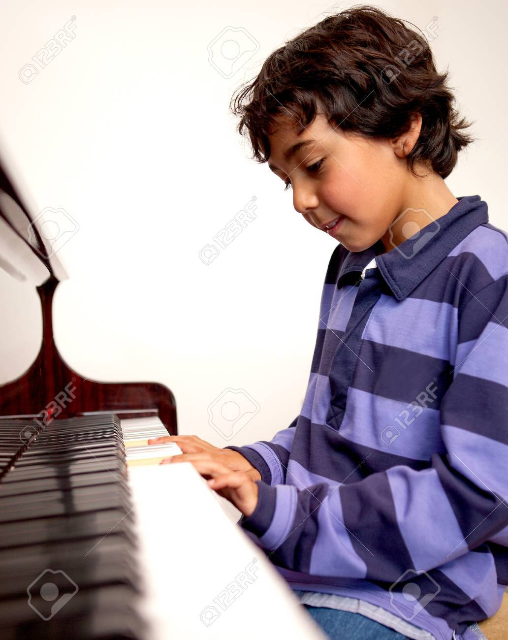 14024276-Cute-boy-playing-the-piano-at-home--Stock-Photo-music.jpg