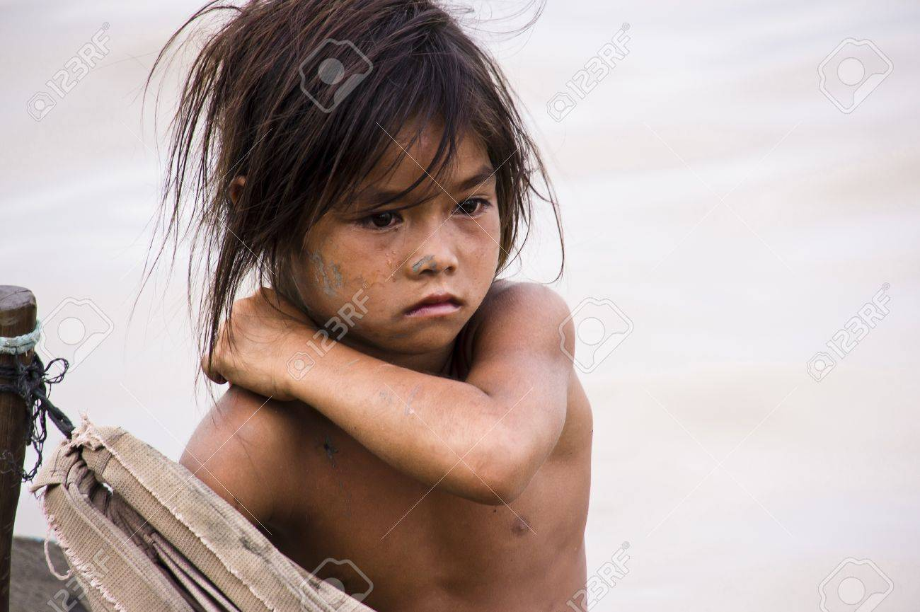 CAMBODIA – May 2012: A young poverty girl scratching herself on a rough wooden boat sailing in Tonle Sap Lake, Cambodia, May 2012.  Living conditions in the area are difficult - Cambodia Standard-Bild - 14145569