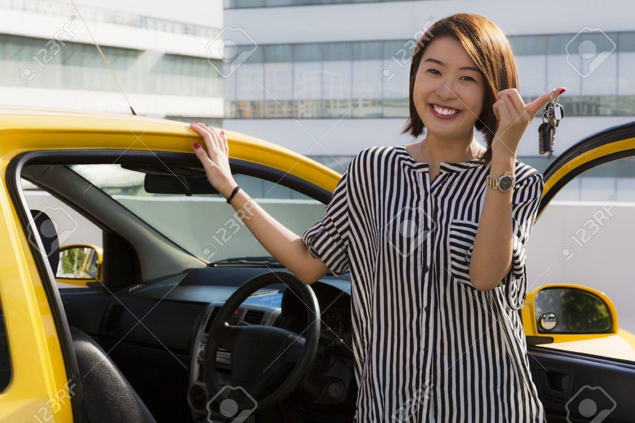 A young Asian lady holding car keys with her yellow car Standard-Bild - 19906567