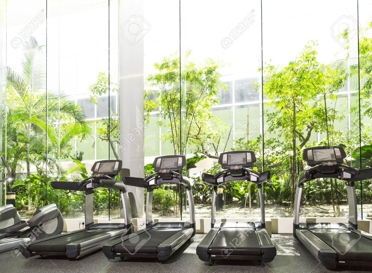 Four Treadmill in a gym with high ceiling in front of a big glass window Standard-Bild - 21303401