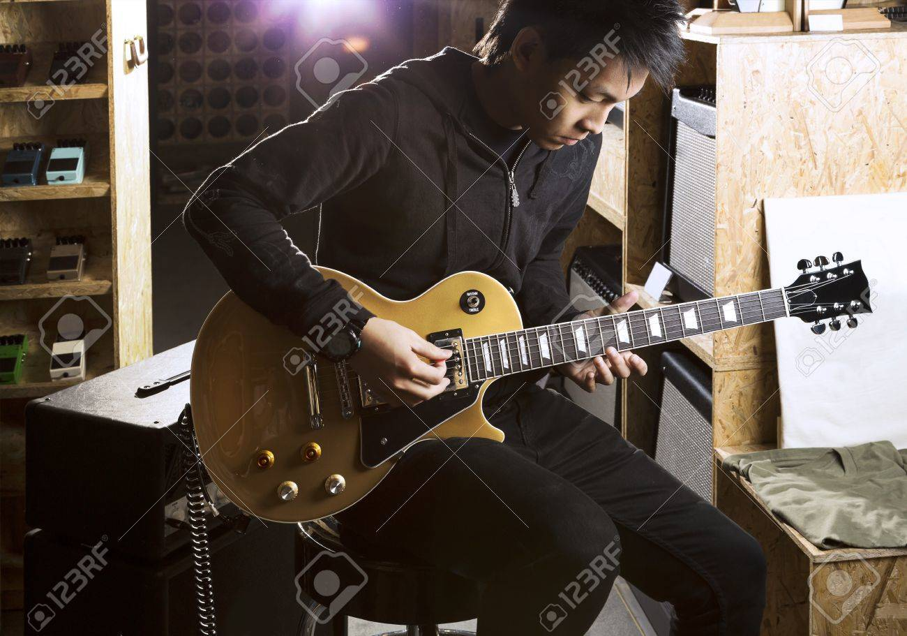 A young asian teenager playing electric guitar with a spotlight shining from the back. Standard-Bild - 21461428