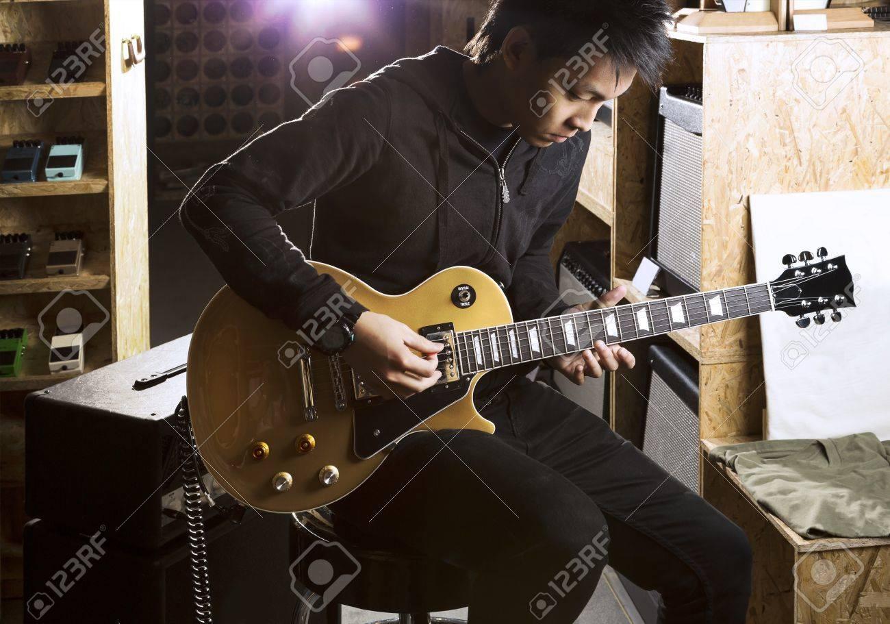 Eine junge asiatische Teenager, die elektrische Gitarre mit einem Scheinwerfer scheint von der Rückseite. Standard-Bild - 21461428