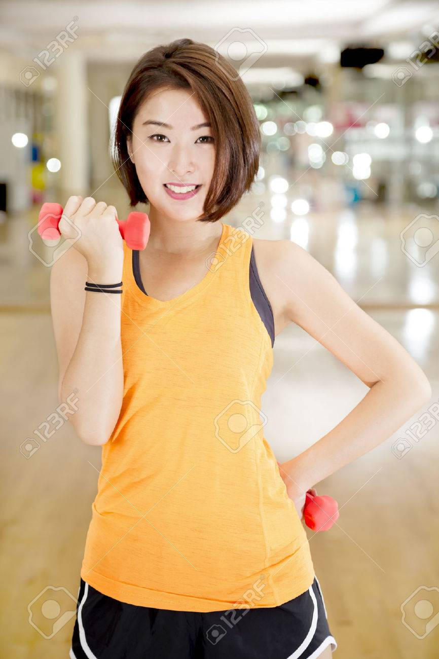 An Asian lady doing weight lifting exercise in a gym. Standard-Bild - 22549480