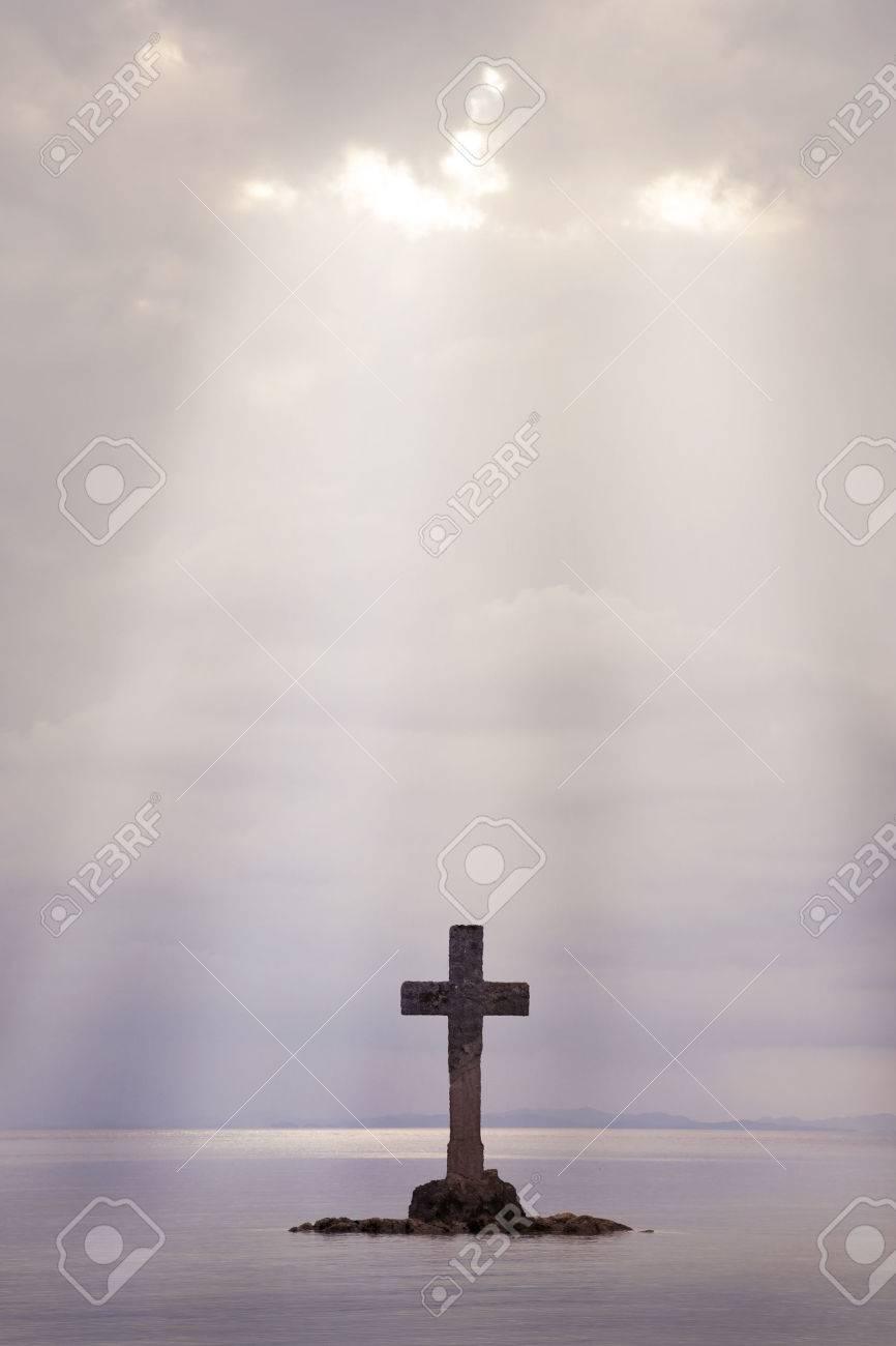 Ein Kreuz aus Stein errichten auf einer Insel vor der Küste Standard-Bild - 24061741