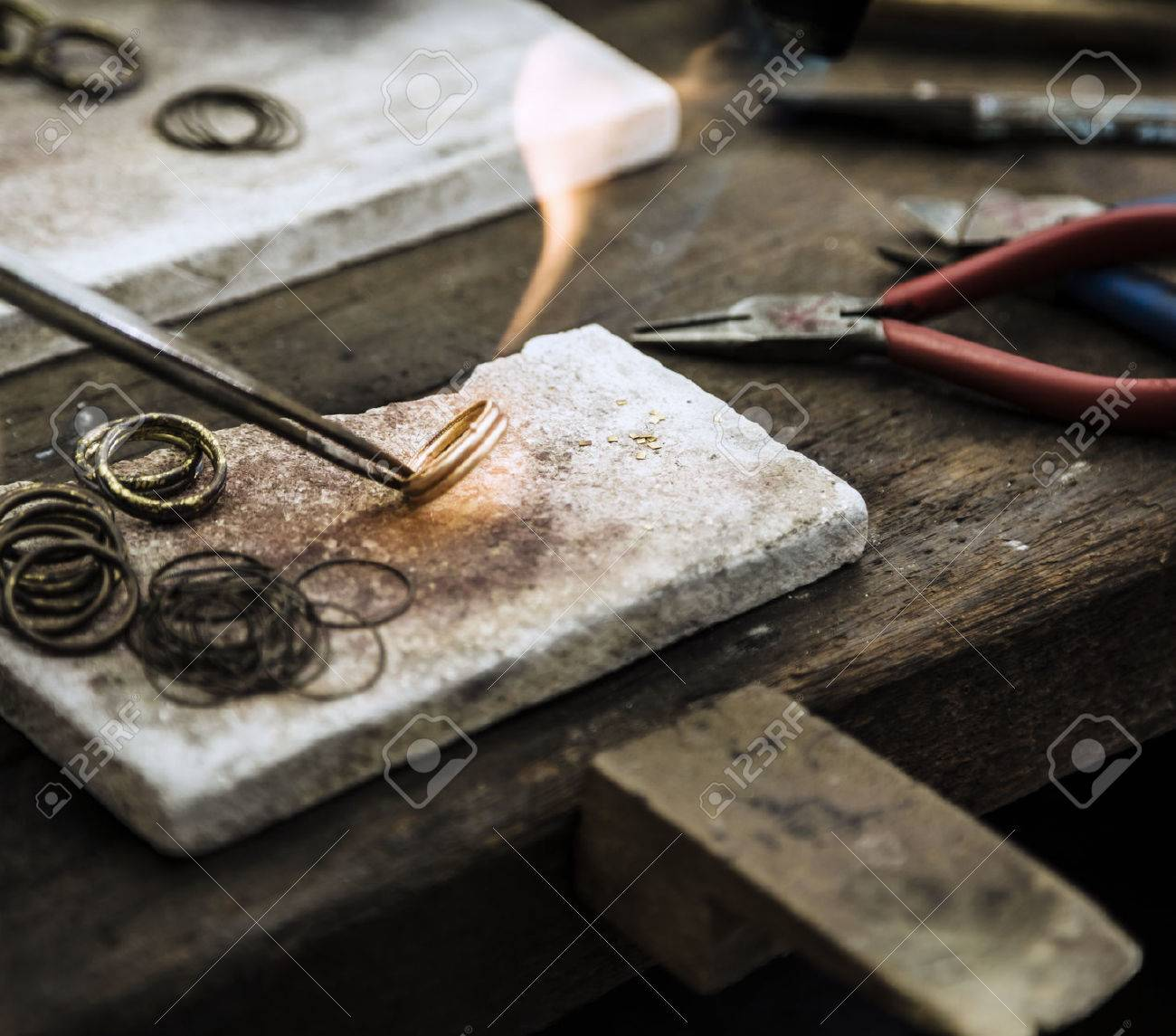 Close up of Jeweler crafting golden rings with flame torch. Standard-Bild - 26047350