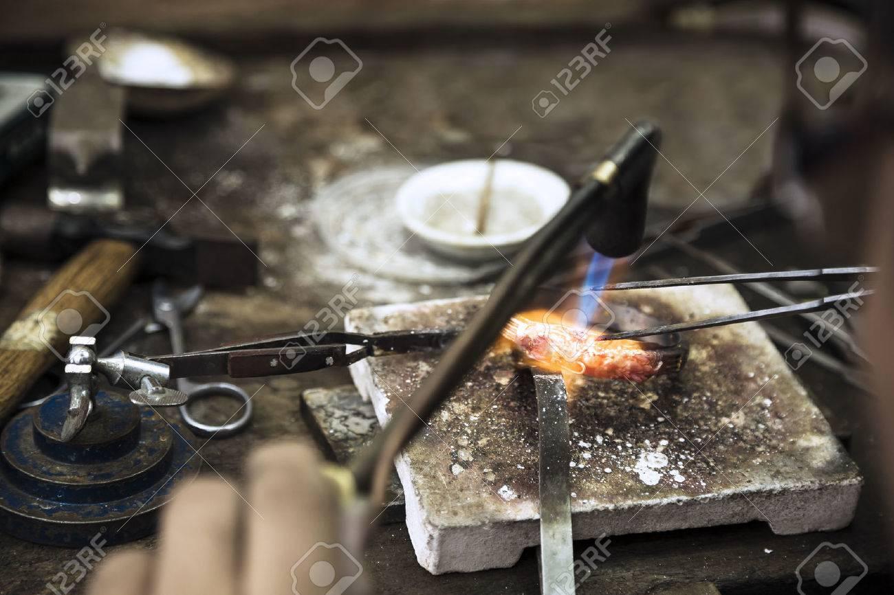Nahaufnahme von Juwelier Crafting goldene Ringe mit Flamme Fackel. Standard-Bild - 26047449