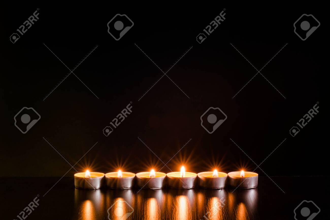 Burning candles on black background - 120575549