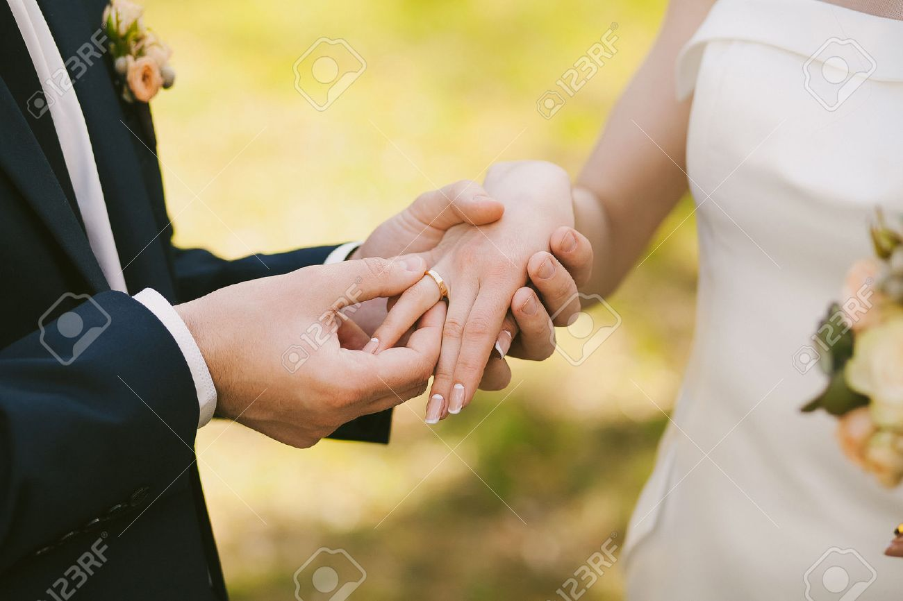 Wedding Rings And Hands Of Bride And Groom. Young Wedding Couple At  Ceremony. Matrimony