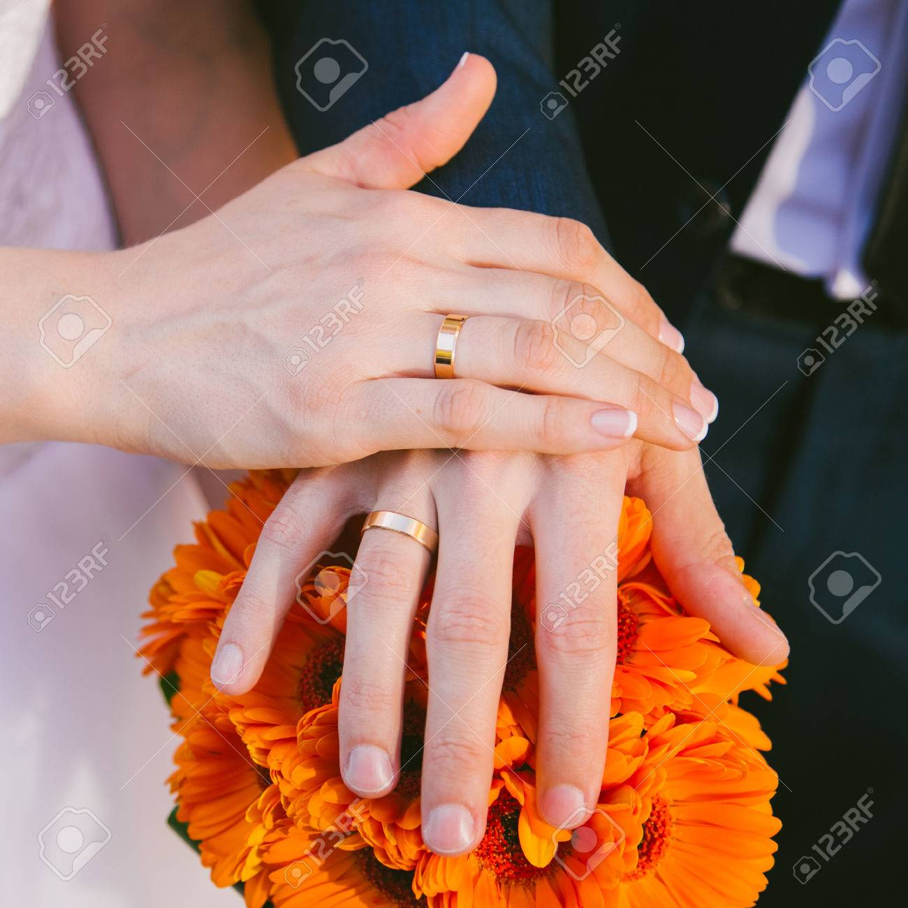 Brides And Grooms Hands With Wedding Rings On Fingers Over Wedding ...