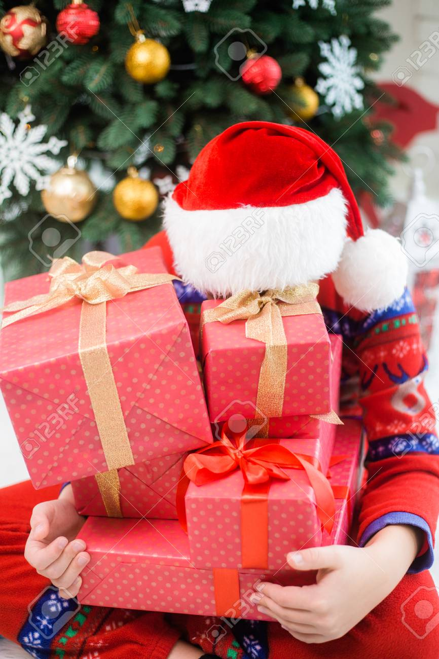 Funny Little Child In Christmas Red Hat Hiding Behind Pile Of Holiday Presents Green Beautiful